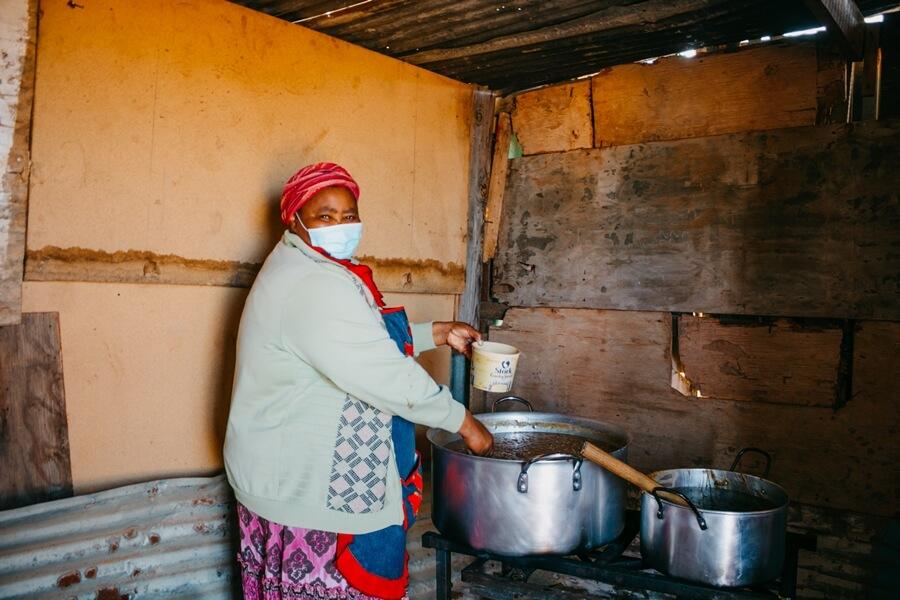 Woman stirring food at soup kitchen